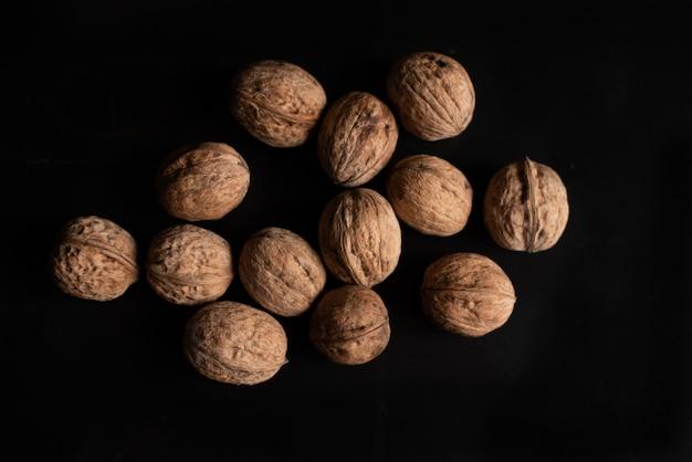 Veel walnoten op zwarte achtergrond en notenkraker.