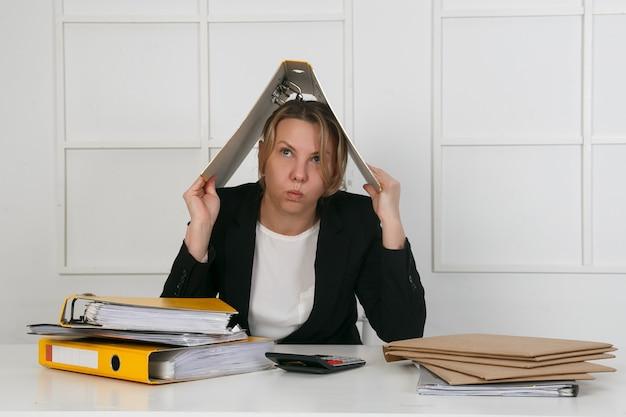 Veel werk wacht op vermoeide en uitgeputte vrouw. enorme stapel documentenmappen, hoofdpijn en depressie