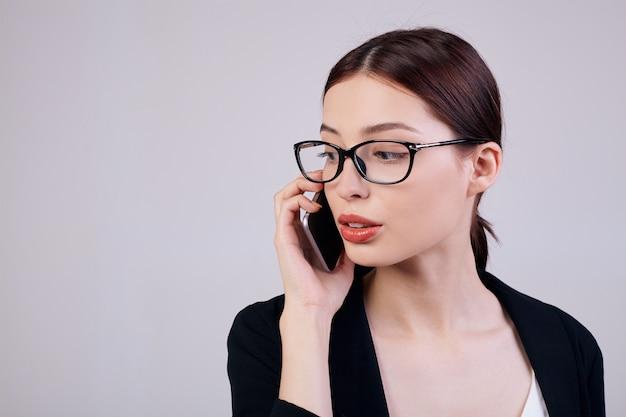 Veel werken. drukke werker. kopieer ruimte. aangenaam ogende rustige vrouw met een mobiele telefoon in haar rechterhand staat op een grijze rug in een zwart jasje, een t-shirt en een bril.