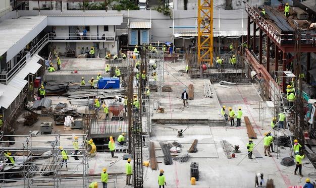 Veel werknemers op bouwplaats en bouwmachines