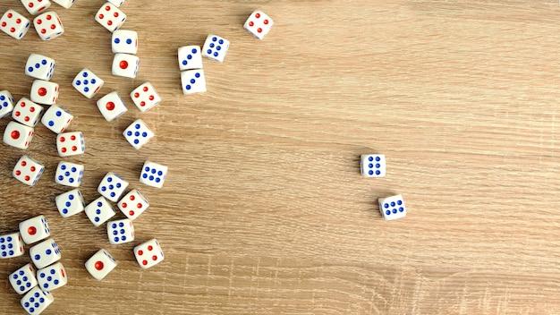 Veel witte dobbelstenen met rode en blauwe stippen op houten tafel. casino gokken concept. detailopname. binnen.