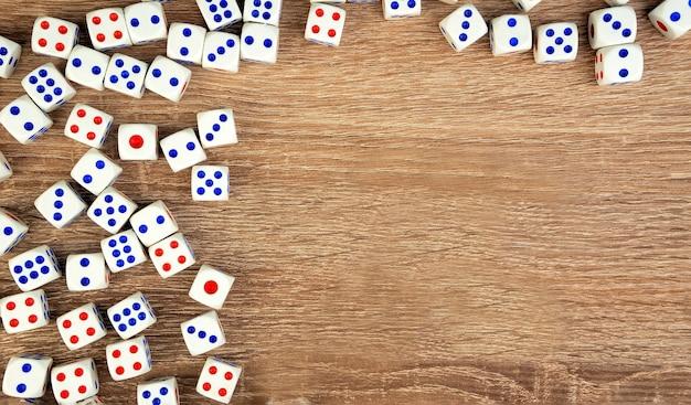 Veel witte dobbelstenen met rode en blauwe stippen op houten tafel. casino gokken concept.