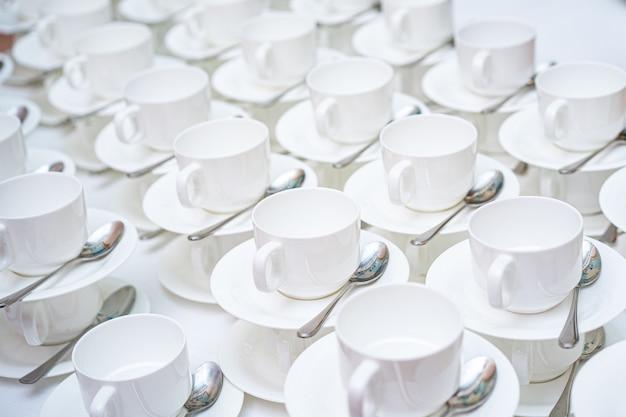 Veel witte koffiekopjes. bovenaanzicht op veel gestapeld in rijen van lege schone witte kopjes voor thee of koffie