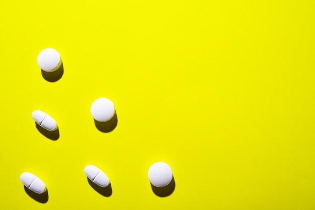 Veel witte medische pillen op een rij op een gele ruimte. pillen werpen een schaduw.