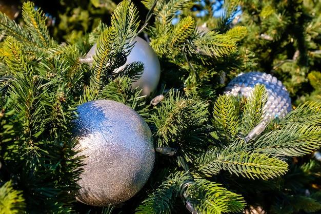 Veel witte nieuwjaarsballen en guirlande op een takken van kunstmatige kerstboom buitenshuis