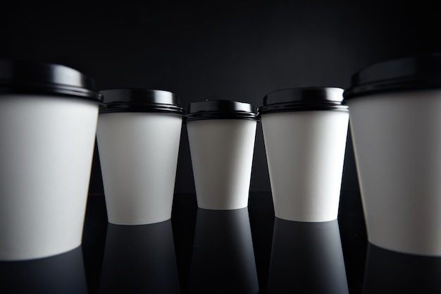 Veel witte papieren bekers voor warme dranken die zijn afgesloten met doppen die in parallax-perspectief worden gepresenteerd