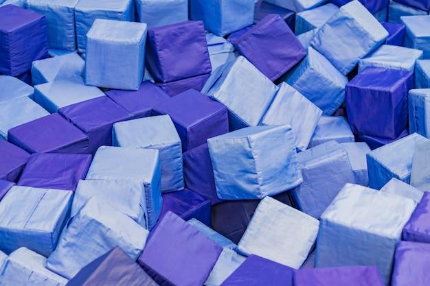 Veel zachte blauwe blokken in een droog kinderbad in de speeltuin. geometrisch speelgoed.