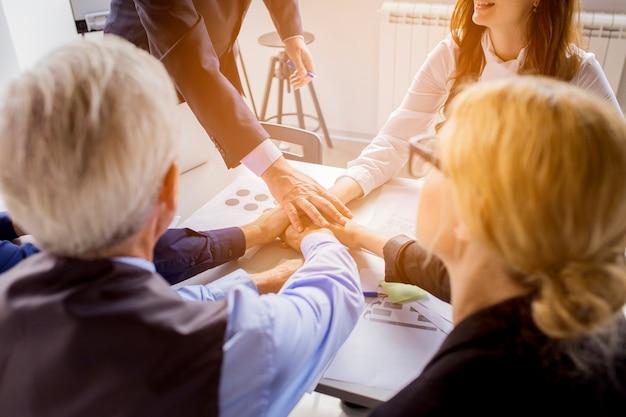 Veel zakenlui bij handen samen op tafel in het kantoor