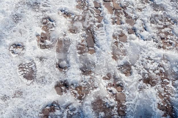 Veel zolenafdrukken bevroren op de stoep in een mengsel van sneeuw en ijs