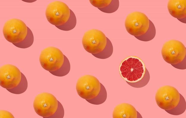 Veel zonovergoten grapefruit gerangschikt in repetitief patroon met schaduw op abstracte pastel kleurrijke achtergrond
