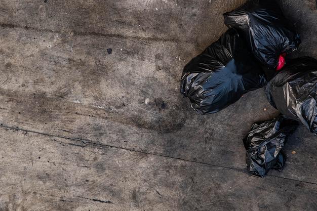 Veel zwarte vuilniszakken die op de stoep zijn vastgebonden