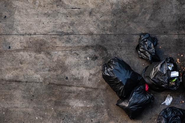 Veel zwarte vuilniszakken die vastgebonden zijn. op de stoep, ongeveer het voetpad, gezien vanaf het bovenaanzicht