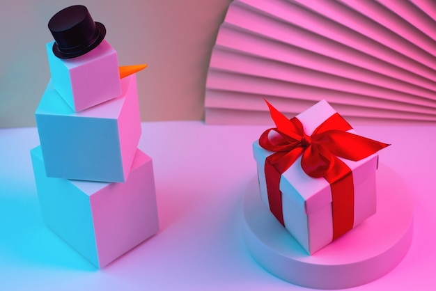 Veelhoekige sneeuwpop van kubussen en cadeau verlicht met neonlicht