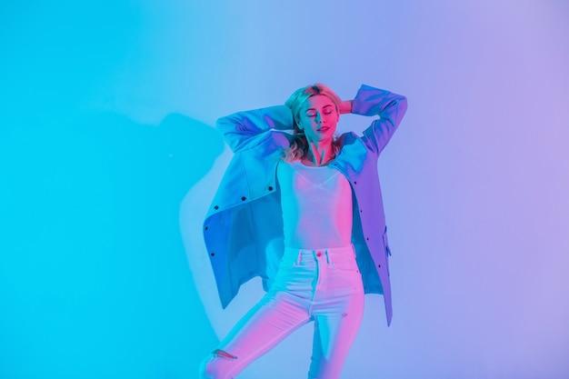 Veelkleurig creatief portret van een jong, vrij sexy vrouwenmodel in modieuze elegante bedrijfskleding met een blauwe blazer, blouse en witte spijkerbroek in de studio met felle neonroze lichten