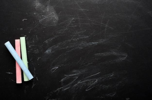 Veelkleurig krijt op een geschilderd zwart bord. schoolbestuur, conceptuele achtergrond. kopieer ruimte, bovenaanzicht, plat lag.