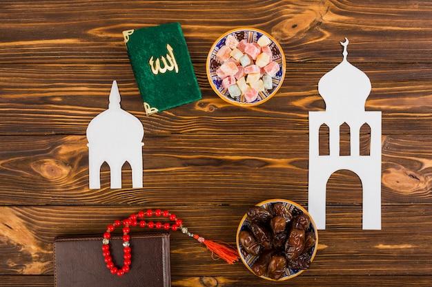 Veelkleurig lukum; kuran boek; bidparels en dagboek met uitgesneden witte islamitische moskee op houten bureau