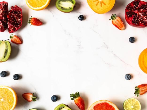 Veelkleurig seizoensgebonden gezond natuurlijk fruitframe met dadelpruim, bosbessen, sinaasappel, kiwi, aardbeien, grapefruit, granaatappel, sinaasappelplakken.