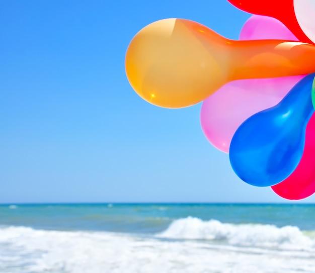 Veelkleurige ballonnen tegen de zee