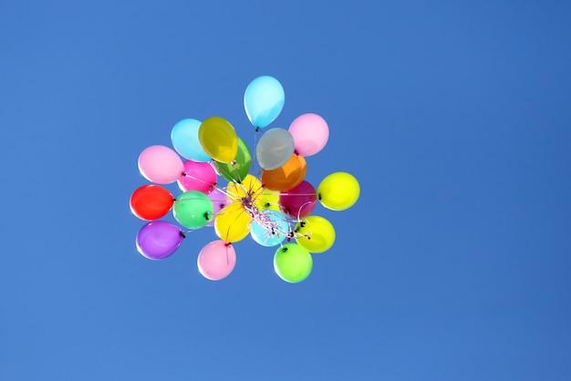 Veelkleurige ballonnen vliegen in de blauwe lucht