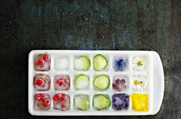 Veelkleurige bevroren ijsblokjes met fruit, bloemen en groenten op een donkere achtergrond in de vorm van ijs