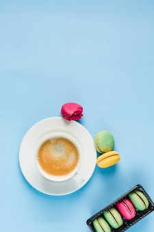 Veelkleurige bitterkoekjes met een witte kop koffie op een blauwe copyspace, bovenaanzicht, plat lag met copyspace