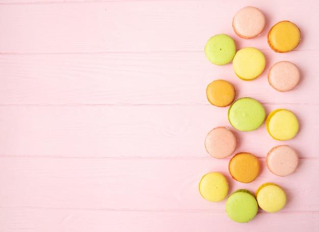 Veelkleurige bitterkoekjes op roze achtergrond.