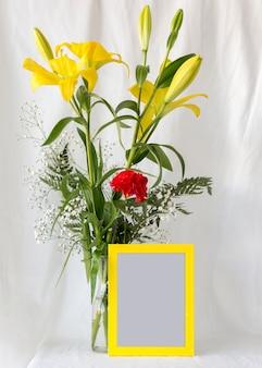 Veelkleurige bloemen in bloemenvaas met leeg leeg fotokader voor wit gordijn