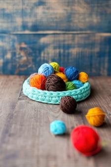 Veelkleurige bollen garen in en bij de gebreide bank