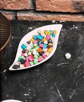 Veelkleurige bonbonsnoepjes (balsuikergoed) binnen witte plaatkom op steenbaksteen