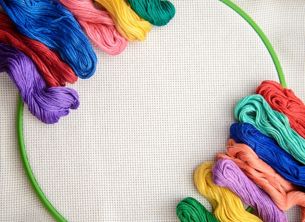 Veelkleurige borduurgaren op een achtergrond van borduurwerk met witte contouren