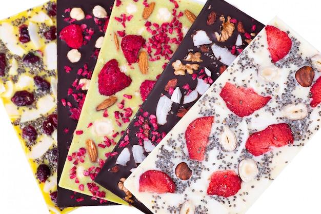 Veelkleurige chocoladerepen met gesublimeerde bessen, kokosnoten en zaden op wit.