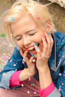 Veelkleurige confetti en kleurrijke manicure op het blonde meisje close-up met een vrolijke bui.
