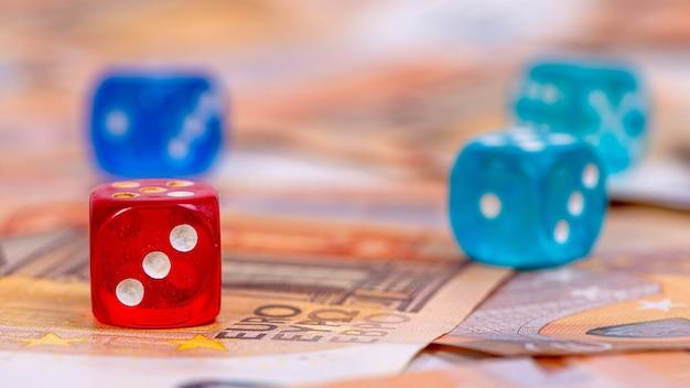 Veelkleurige dobbelstenen close-up op een oppervlak van eurobankbiljetten, zakelijke kansen en risicoconcept