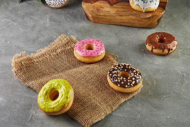 Veelkleurige donuts met glazuur en hagelslag met bloemen op een grijze achtergrond.