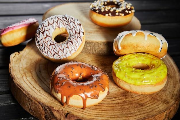 Veelkleurige donuts met glazuur en hagelslag op houten onderzetters op een zwarte achtergrond.