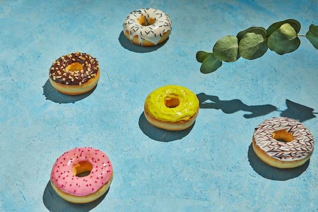 Veelkleurige donuts met glazuur, hagelslag en bladeren op blauwe achtergrond.
