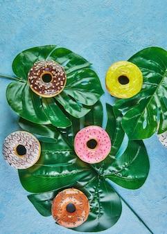 Veelkleurige donuts met glazuur, hagelslag liggen op monsterabladeren op blauwe achtergrond.