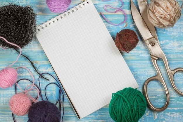 Veelkleurige draad met wol en schaar op een houten tafel.