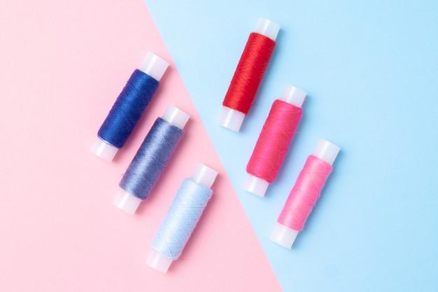 Veelkleurige draadrollen op roze blauw.