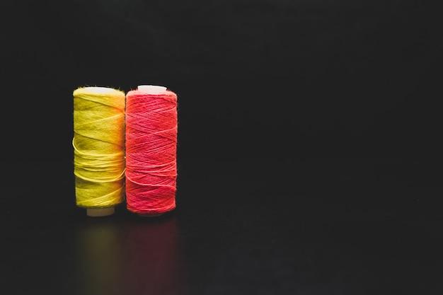 Veelkleurige draden op een zwarte naaien