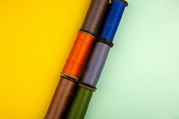 Veelkleurige draden voor het naaien op een geelgroene vloer