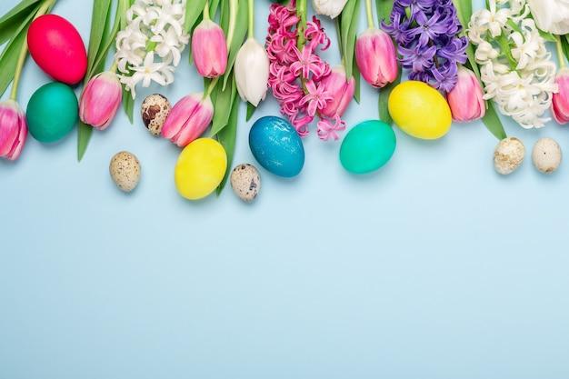 Veelkleurige eieren en lente bloemen tulpen en hyacinten op een blauwe achtergrond. pasen concept. kopieer ruimte - afbeelding