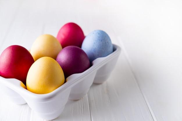 Veelkleurige eieren in een wit dienblad
