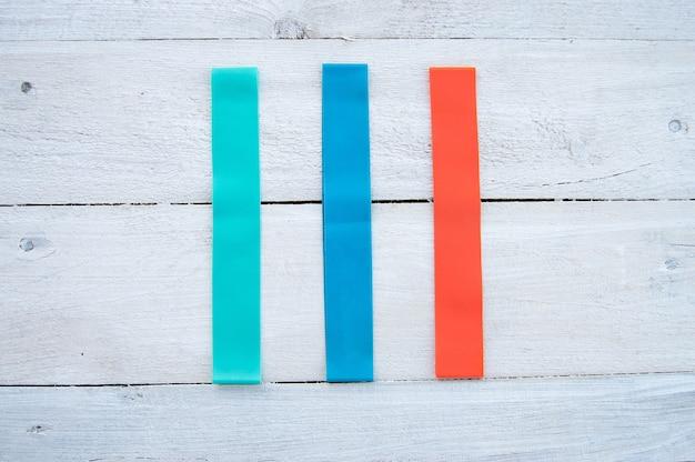 Veelkleurige elastische elastiekjes voor fitness op een wit hout. plat leggen