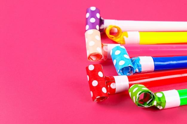 Veelkleurige feestblazers op roze kleur. veelkleurige feestfluitjes. decor voor een verjaardag.