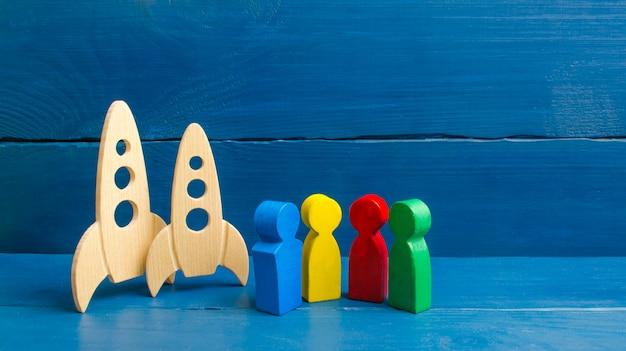 Veelkleurige figuren van mensen staan in de buurt van raketten.