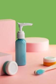 Veelkleurige flessen en pot met tandenborstel op roze decoratie en groene muur