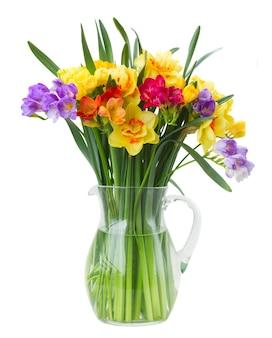 Veelkleurige fresia en narcisbloemen in vaas