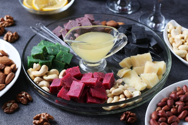 Veelkleurige gastronomische kaas, olijven, noten, honing en gesneden citroen op donkere achtergrond. voorgerecht voor een wijnfeest. detailopname