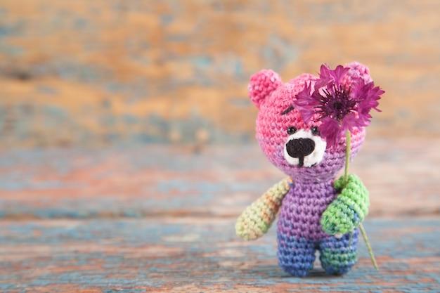 Veelkleurige gebreide kleine beer met korenbloemen op een oude houten achtergrond.
